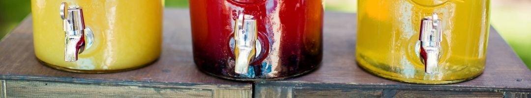 Drei Getränkespender aus Glas mit Säften gefüllt
