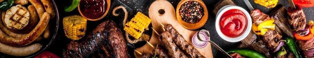 Holzbretter mit Fleisch, Würstchen, Saucen und Mais