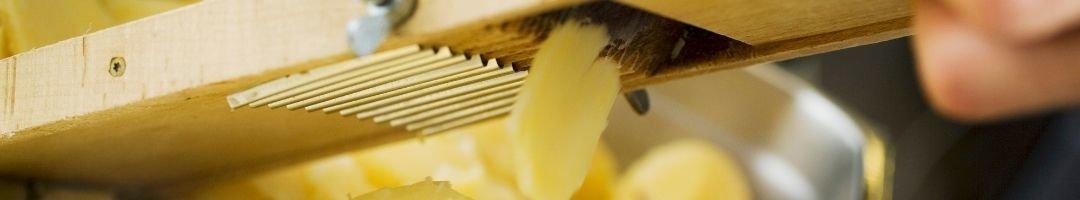 Mandoline, die eine Kartoffel in Scheiben reibt