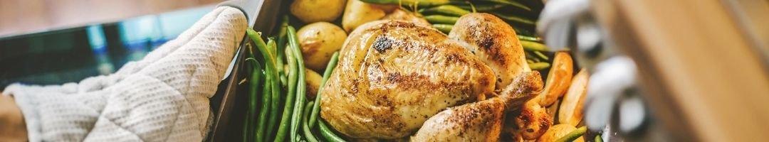 Bräter mit Hähnchen, Kartoffeln und Bohnen, der in den...