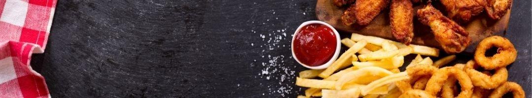 Holzbrett mit Pommes, Chicken Wings und Ketchup