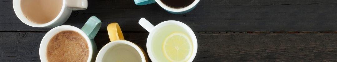Tassen mit Tee, Kaffee, Cappuchino und Heißer Zitrone
